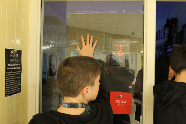 Student Scanning Hand for Entry to Escape Room